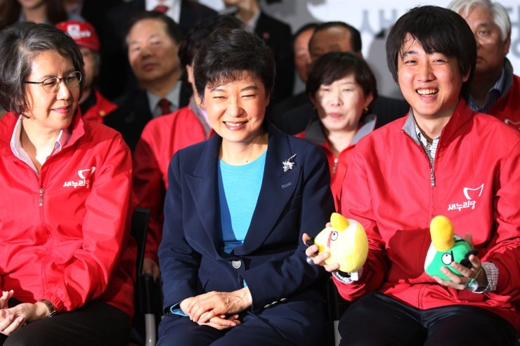 Lee Jun-seok, right, then a member of the emergency committee of the Saenuri Party, a predecessor of the main opposition People Power Party, watches an exit poll broadcast after the 19th general election, seated beside Park Geun-hye, center, then-leader of the Saenuri Party, in this April 2012 file photo. Yonhap