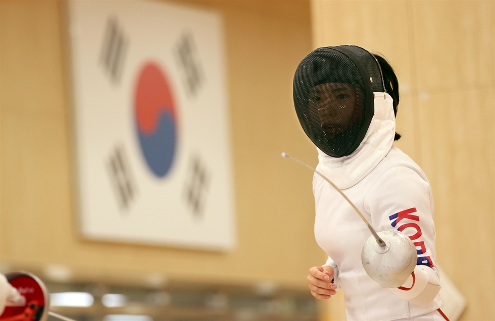 A fencer holds a protective mask bearing the 'taegeuk' pattern as seen on Korea's national flag at the Jincheon National Training Center in North Chungcheong Province, June 28. The opening ceremony for the Tokyo Olympics is scheduled for July 23, with 24 days remaining. Yonhap