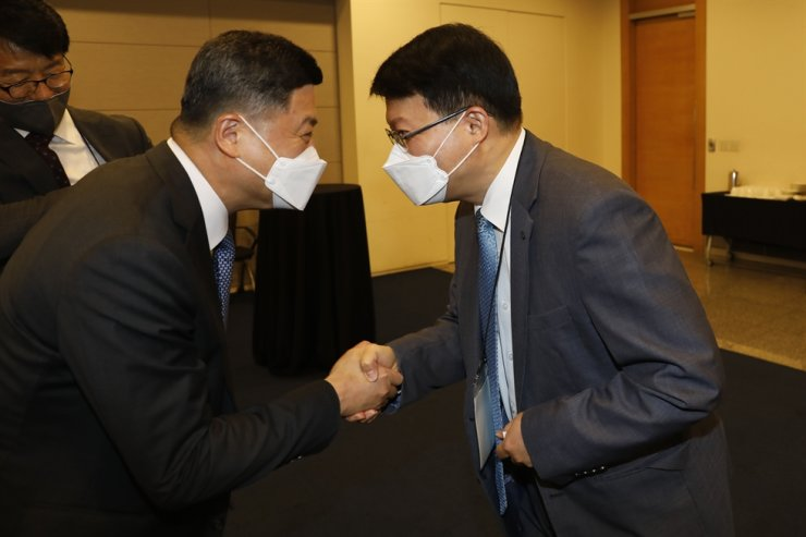 Woori Bank CEO Kwon Kwang-seok, left, shakes hands with Korea Investment Corporation (KIC) Chairman Jin Seoung-ho during a VIP meeting during the forum. Korea Times photo by Shim Hyun-chul
