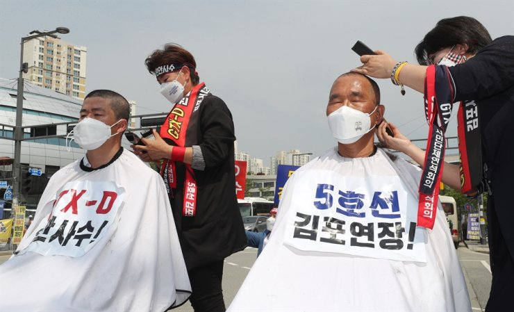 Two members of Gimpo City Council have their heads shaved during a protest against the government's decision not to extend the GTX-D line, near the Ministry of Land, Infrastructure in Sejong, June 2. Yonhap