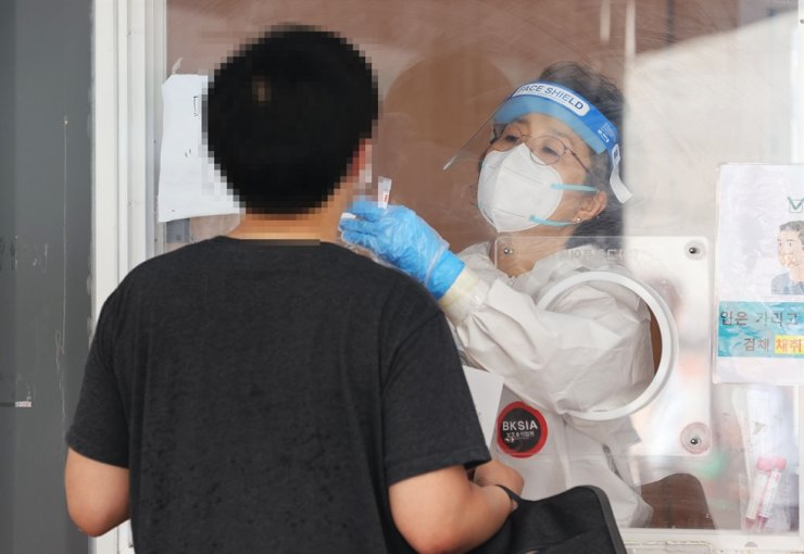 A medical worker takes samples for COVID-19 testing at a makeshift center near Seoul Station, June 13. Yonhap