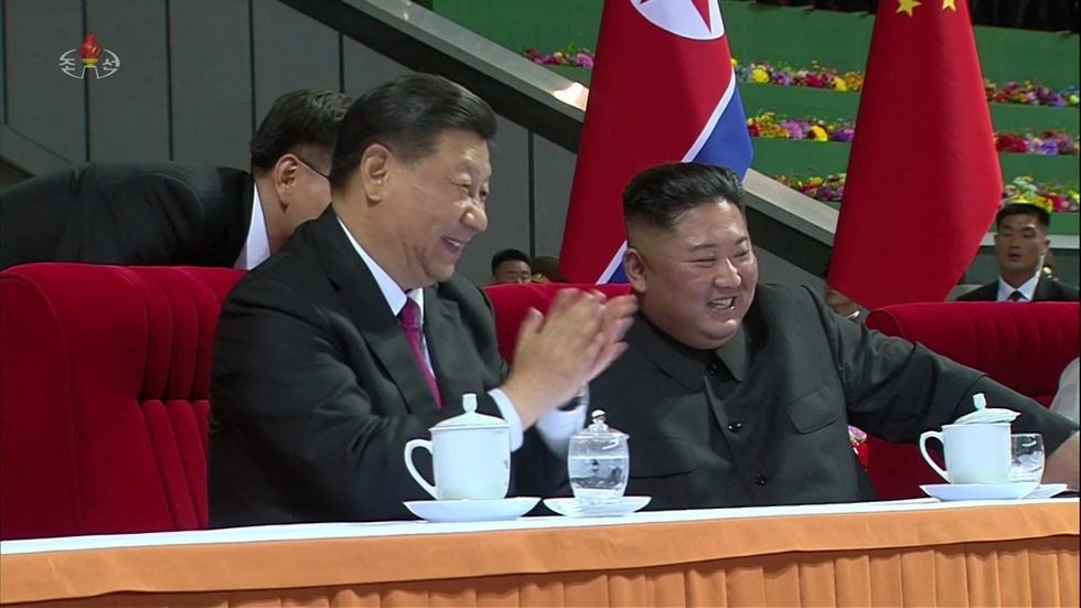 Officials from China and North Korea look at photos of Chinese President Xi Jinping and North Korean leader Kim Jong-un during an exhibition held in the Chinese embassy in Pyongyang, Monday, in this photo released by North Korea's official Korean Central News Agency, Tuesday. Yonhap
