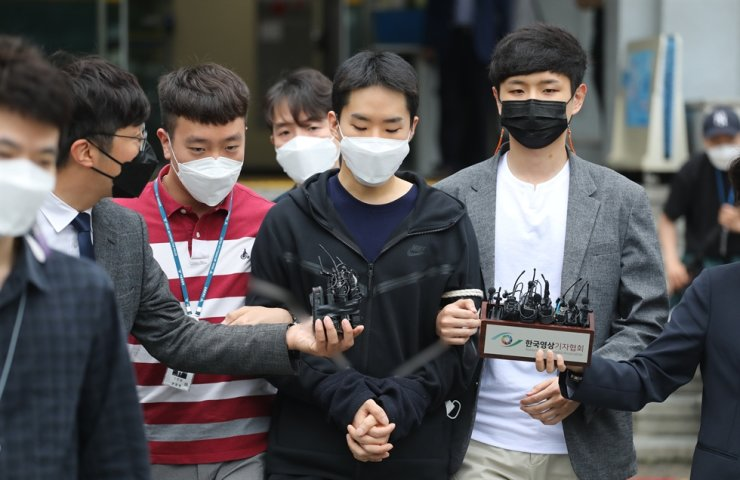 Kim Young-jun, who is accused of filming and distributing nude photos and videos of boys and men, comes out of Jongro Police Station in Seoul, June 11. / Yonhap