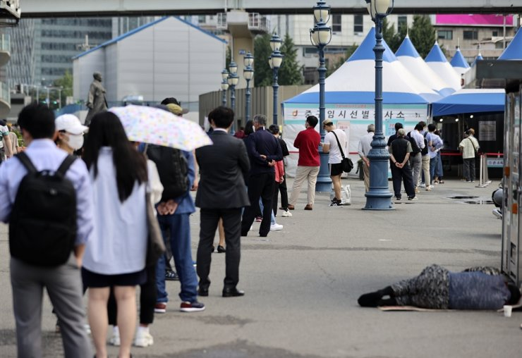 Citizens wait in line for coronavirus testting at a temporary testing site in front of Seoul Station, Wednesday. Yonhap