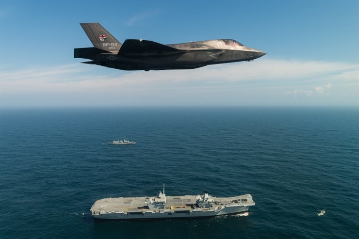 An F-35B flies over the British Royal Navy's aircraft carrier, the HMS Queen Elizabeth. Courtesy of Lockheed Martin