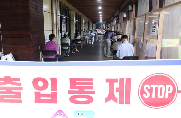 People wait to get tested for COVID-19 at a testing center in Songpa District, Seoul, June 24. Yonhap
