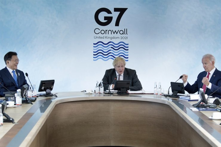 President Moon Jae-in, left, and U.S. President Joe Biden, right, listen to Britain's Prime Minister Boris Johnson during a working session at the G7 summit in Carbis Bay, Cornwall, England, June 12. AP-Yonhap