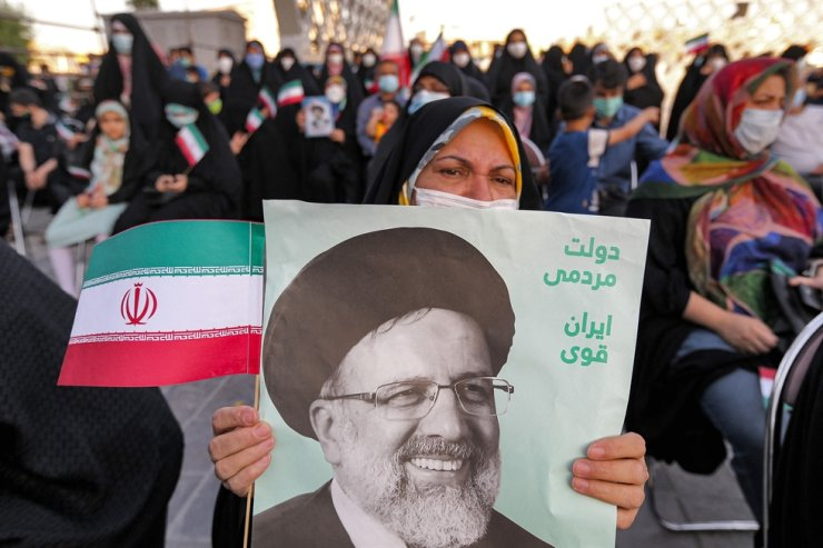 A woman holds a poster of Iran's newly-elected president Ebrahim Raisi, with text in Persian reading 'government of the people, strong Iran', as supporters celebrate his victory in Imam Hussein square in the capital Tehran, June 19. AFP-Yonhap