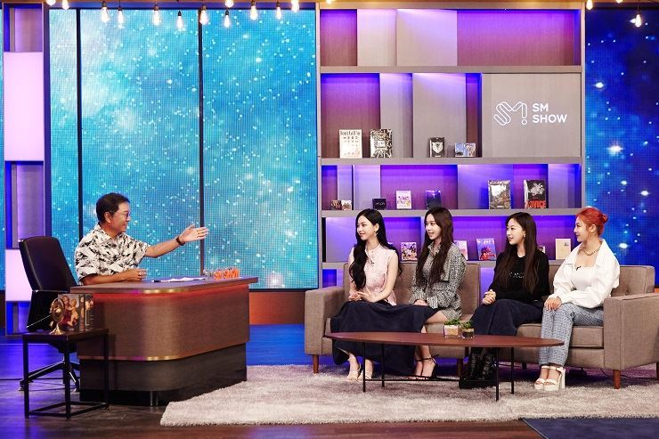 SM Entertainment founder/producer Lee Soo-man, left, talks with the members of girl group aespa during 'SM CONGRESS 2021,' Monday. Courtesy of SM Entertainment