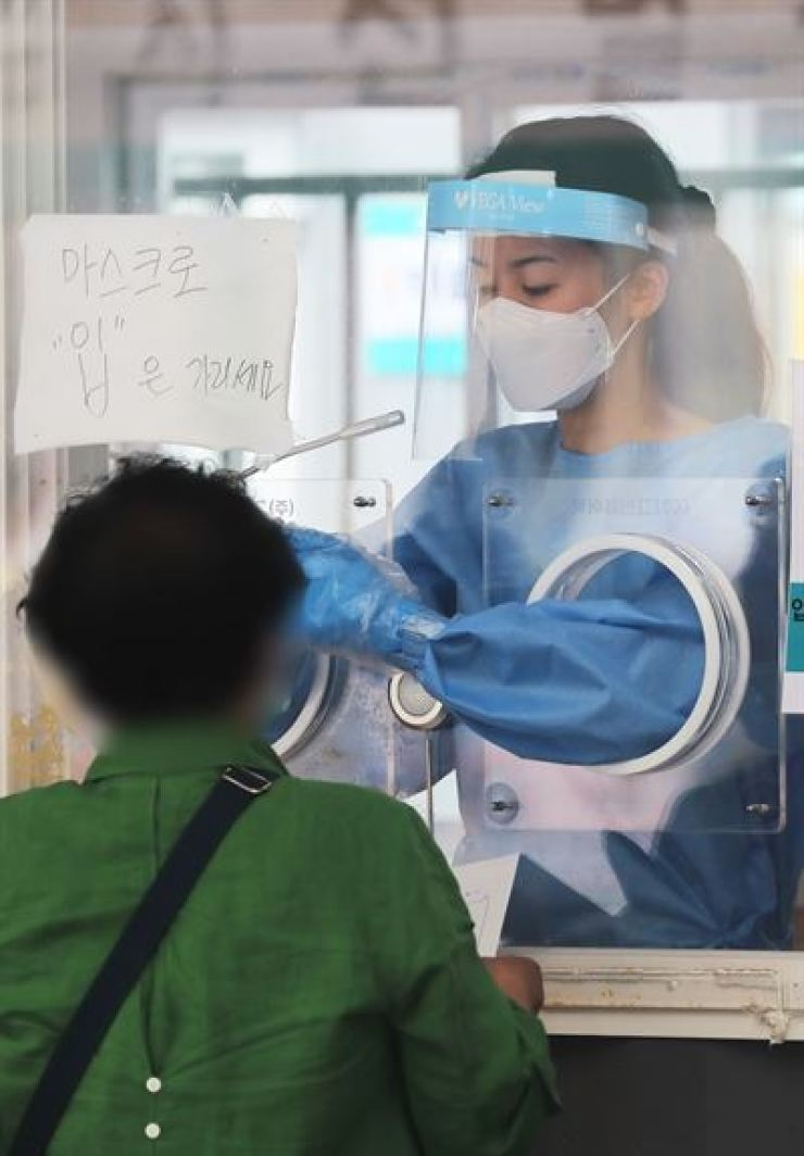 A medical worker takes test samples for COVID-19 at a makeshift testing center near Seoul Station, June 7. Yonhap