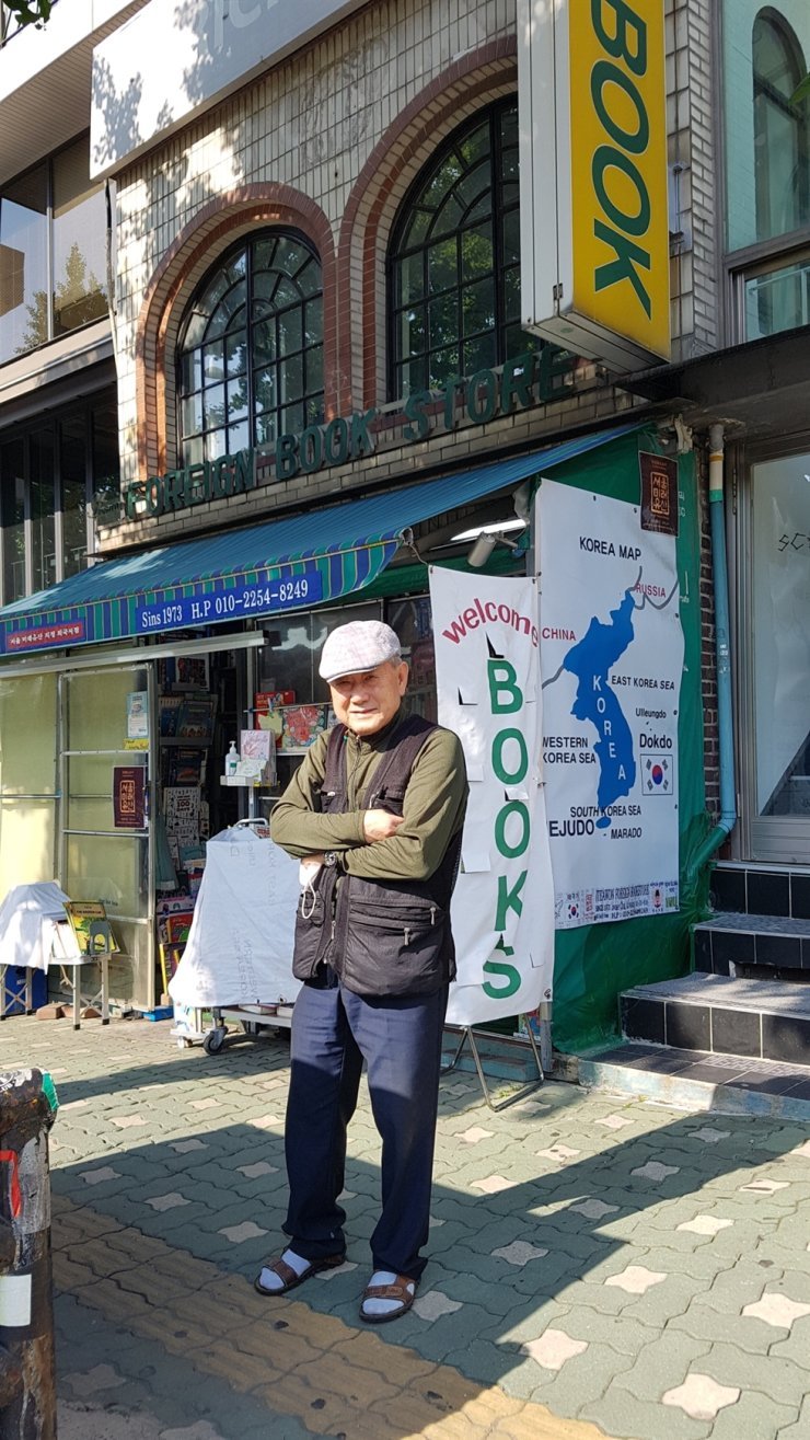 Bibliophile Choi Ki-woong poses in front of his 48-year-old book store in Noksapyeong / Courtesy of Richard Pennington