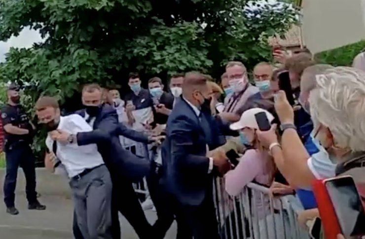 French President Emmanuel Macron is protected by a security member after getting slapped by a member of the public during a visit in Tain-L'Hermitage, France, in this still image taken from video, June 8. Reuters-Yonhap