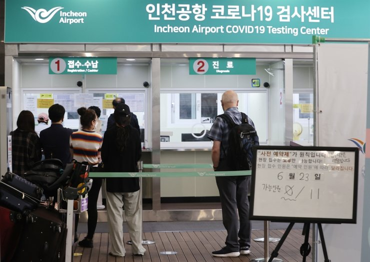 Outbound travelers wait to receive a coronavirus test at a testing center at Incheon International Airport, Thursday. Yonhap