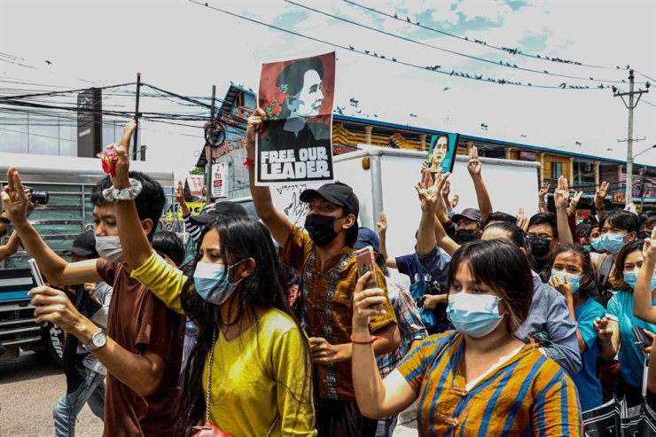 Protesters make the three-finger salute and hold posters of Myanmar's detained civilian leader Aung San Suu Kyi to mark her birthday as they take part in a demonstration against the military coup in Yangon, June 19. AFP-Yonhap