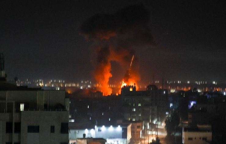 Explosions light-up the night sky above buildings in Gaza City as Israeli forces shell the Palestinian enclave, June 16. AFP-Yonhap