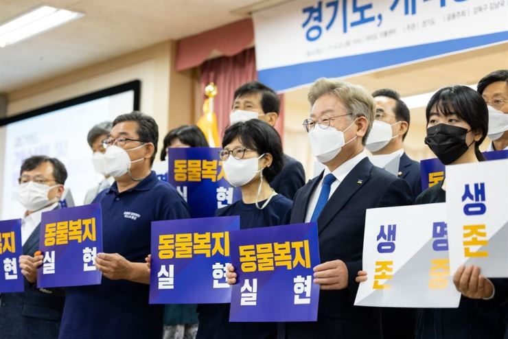 Gyeonggi Province Governor Lee Jae-myung, front row second from right, holds a placard that reads, 'Realizing animal welfare,' during a debate on the matter of improving the legal system to ban dog meat consumption, co-hosted by the provincial government and 30 lawmakers, at Eroom Center in Yeouido, Seoul, Tuesday. Yonhap