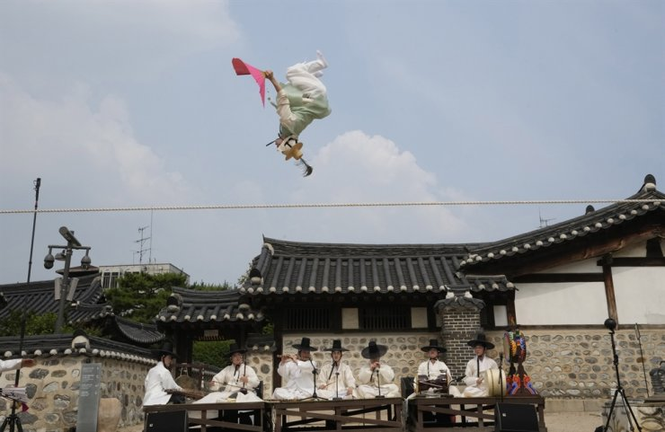 A tightrope walker Nam Chang-dong performs 'Jultagi,' or tightrope walking, at the Namsan Hanok village in Seoul, June 14. Korea's daily new COVID-19 cases remained under 400 for the second day Tuesday on fewer tests over the weekend as the country's vaccination drive picks up steam with inoculations likely to top 13 million soon. AP-Yonhap