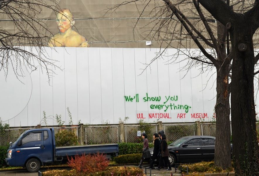 A white guy with a nosebleed peers over the construction fence at the National Museum of Modern and Contemporary Art, Nov. 28, 2012. / Courtesy of Ron Bandun