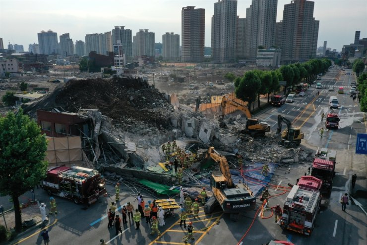 Rescue workers try to extricate people buried under a collapsed building in Gwangju, Wednesday. At least nine people died after the five-story building collapsed during demolition work and buried a bus under the debris. Yonhap