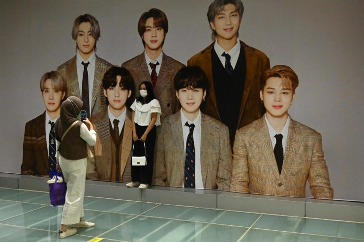 An Indonesian fan of South Korean K-pop boy band BTS poses with a giant poster of the band members at a shopping mall in Jakarta, June 21. AFP-Yonhap