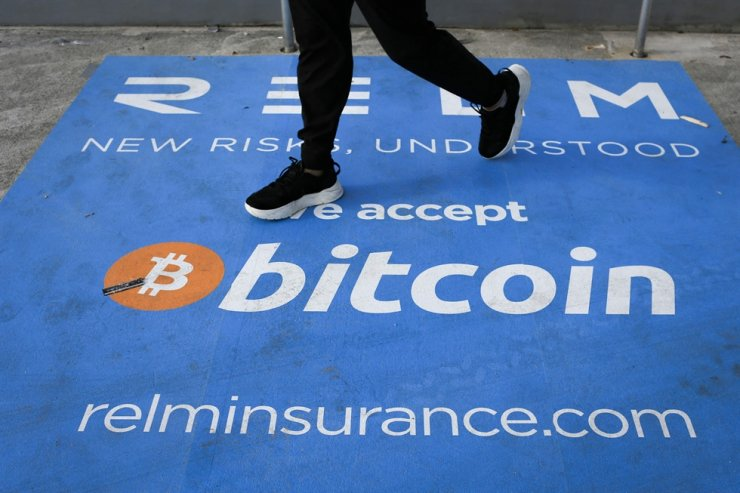 A man walks past a banner with the logo of bitcoin during the crypto-currency conference Bitcoin 2021 Convention at the Mana Convention Center in Miami, Florida, June 4. AFP-Yonhap