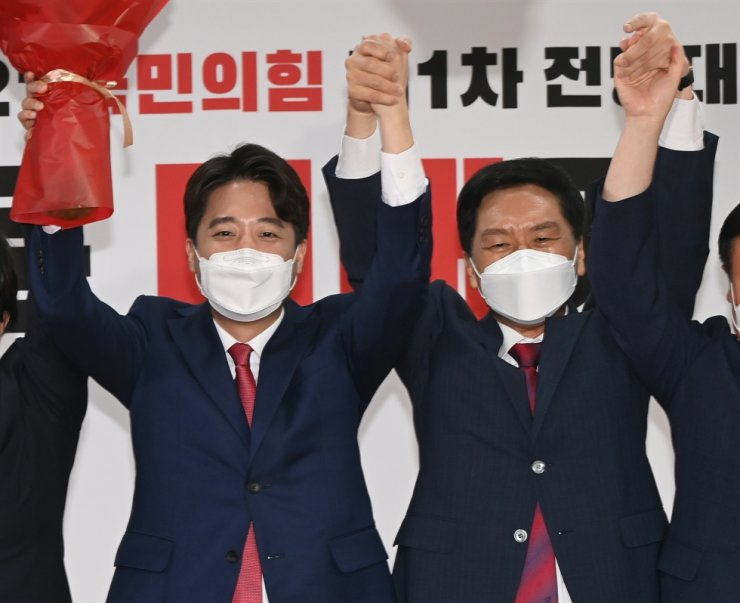 Lee Jun-seok, left, hails after being elected as the leader of the main opposition People Power Party at the party headquarters in Seoul, June 11. Yonhap