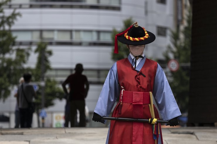 A guard stands at the entrance of Sungnyemun, also known as Namdaemun ― one of the remaining gates that mark the old city of Seoul, then known as Hanseong. The back entrance reopened to the public on June 22, for the first time since the National Treasure was damaged by an arsonist in 2008. The gateway will provide easier access to Namdaemun Market and Seoul Station, said the Cultural Heritage Administration. Korea Times photo by Choi Won-suk