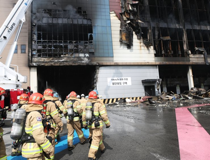 Firefighters enter a Coupang warehouse in Icheon, June 19, after putting out the fire that started there two days ago. Yonhap