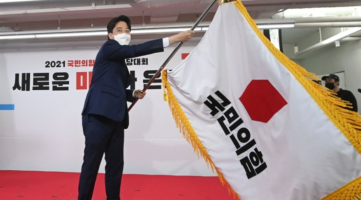 Lee Jun-seok, right, waves the flag of the main opposition People Power Party at the party headquarters in Seoul, Friday, after being elected as its new chairman. Yonhap