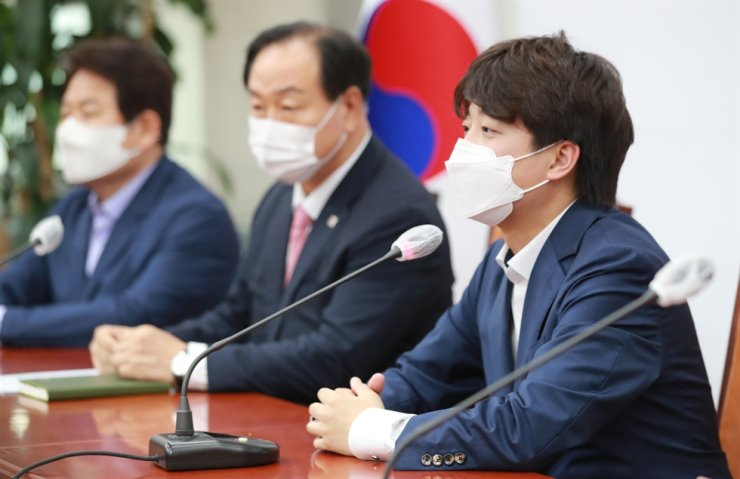 People Power Party Chairman Lee Jun-seok, right, speaks during a preparatory meeting for the party's primary to select its presidential candidate at the National Assembly in Yeouido, Seoul, Friday. Yonhap