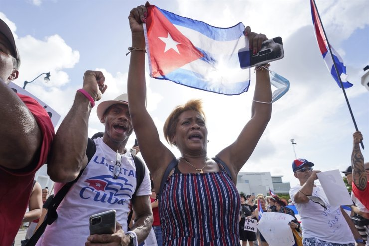 Dulce Diaz, center, and her brother Carlos Diaz, left, demonstrate in Miami's Little Havana neighborhood, July 14, as people rallied in support of anti-government demonstrations in Cuba. AP-Yonhap