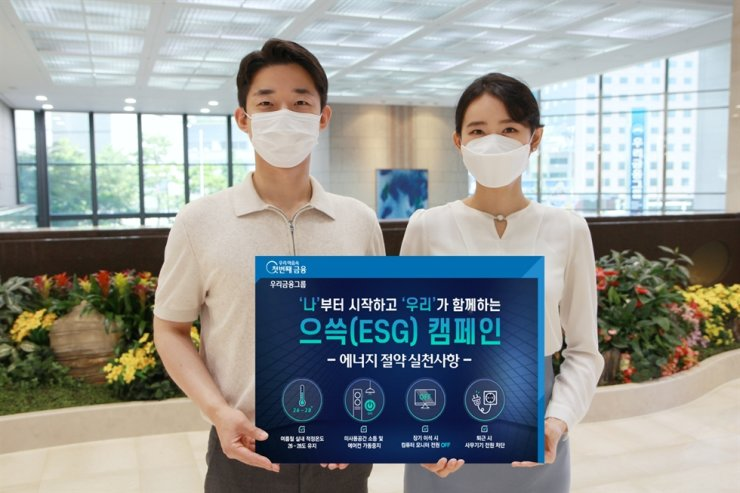 Woori Bank officials hold a sign promoting Woori Financial Group's energy-saving campaign as part of efforts to advance the bank's environmental, social and corporate governance (ESG) drive, Thursday. Courtesy of Woori Bank
