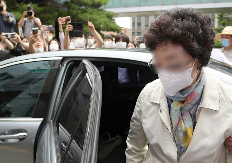 The mother-in-law of former Prosecutor General Yoon Seok-youl, a leading presidential hopeful, gets out of a vehicle to attend her trial at the Uijeongbu District Court in Uijeongbu, Gyeonggi Province, July 2. Yonhap