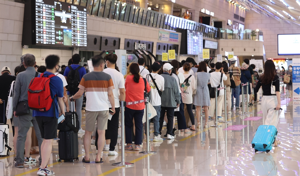 People wait in line for COVID-19 testing at a temporary testing site at Gangnam Public Health Center in southern Seoul, Sunday. Yonhap