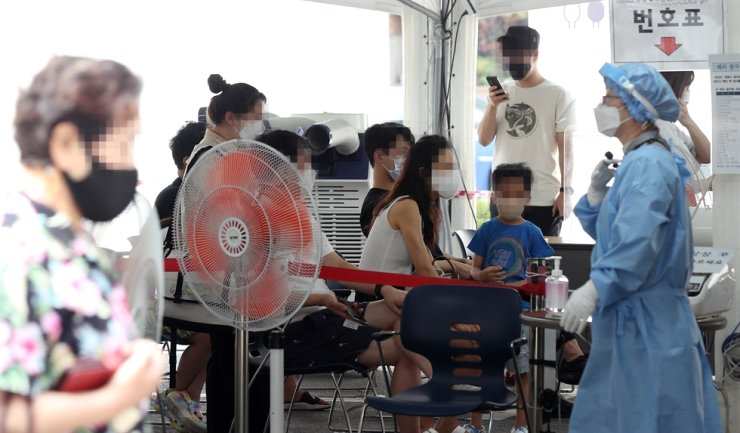 People wait to get tested for COVID-19 at a testing center in Gangnam District, Seoul, July 29. Yonhap