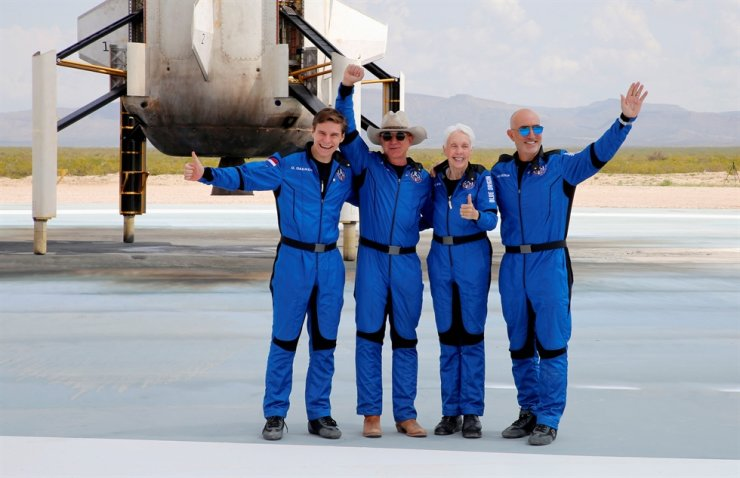 Billionaire American businessman Jeff Bezos, second from left, poses with crew members, from left, Oliver Damen, 18, Bezos, Wally Funk, 82, and his brother Mark Bezos at the landing pad after they flew on Blue Origin's inaugural flight to the edge of space, in the nearby town of Van Horn, Texas, July 20. Reuters-Yonhap