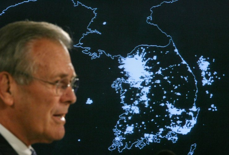 Former U.S. Secretary of Defense Donald Rumsfeld speaks in front of a satellite map of the Korean Peninsula at night during a press briefing at the Pentagon in Washington, Oct. 11, 2006. Rumsfeld died on Tuesday at age 88. Reuters-Yonhap