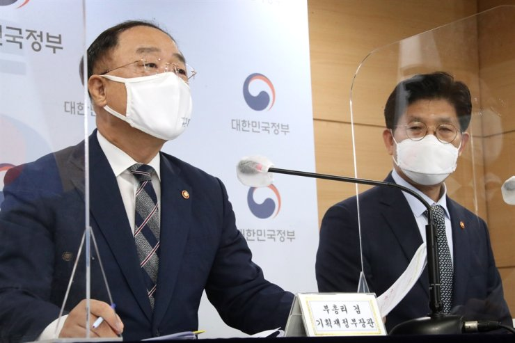 Deputy Prime Minister and Finance Minister Hong Nam-ki, left, speaks during a press briefing at the Seoul Government Complex, Wednesday. Yonhap