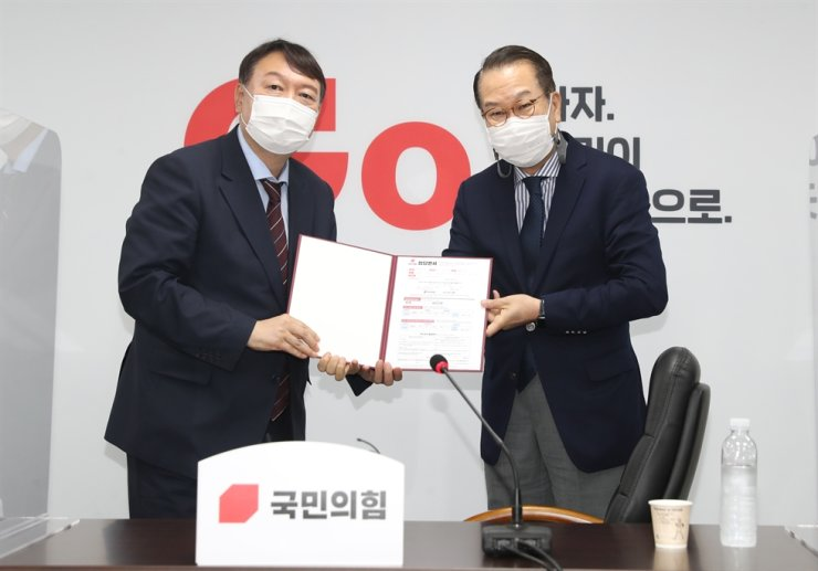 Former prosecutor general Yoon Seok-youl, left, poses with Rep. Kwon Young-se, external affairs committee head of the conservative main opposition People Power Party, after submitting his entry to the party at its headquarters on Yeouido, Seoul, Friday. Yonhap