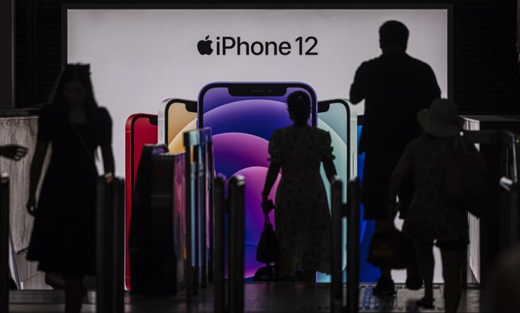 People enter the subway in front of an Apple's iPhone 12 advertisement, in Shanghai, China, Friday. According to the National Bureau of Statistics, China's Consumer Price Index (CPI), which is a main gauge of inflation, rose 1.1 percent year-on-year in June. EPA-Yonhap