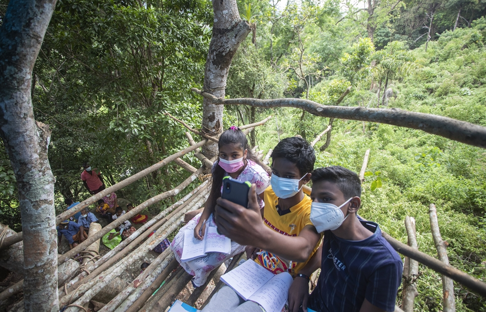 Sri Lankan children walk down a mountain after attending their online lessons in a forest reserve in Bohitiyawa village in Meegahakiwula, Sri Lanka, July 2. Climbing rocks and sitting on tree tops is not part of their curriculum but children in villages surrounding the capital city are doing just that to be able to catch mobile signals to access their online classes. AP-Yonhap