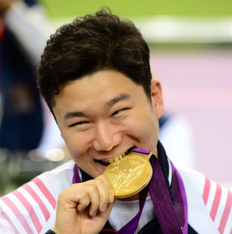 The custom of athletes taking a bite of their hard-won gold medals will no longer be a part of awards ceremonies at the Tokyo Olympics. Korea Times file
