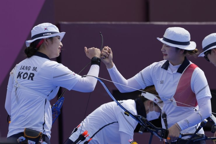 Korea's Jang Min-hee , left, and Kang Chae-young smile during the women's team competition at the 2020 Summer Olympics, July 25, in Tokyo. AP-Yonhap