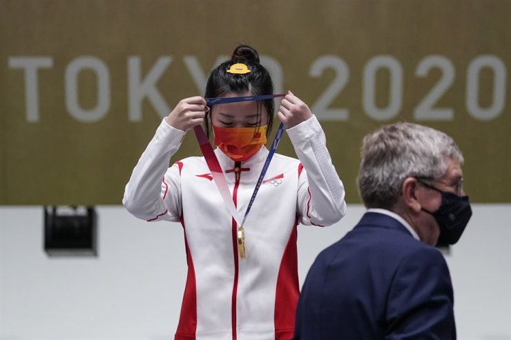 China's Yang Qian puts her gold medal on herself after it was presented by International Olympic Committee President Thomas Bach, after winning the gold in the women's 10-meter air rifle at the Asaka Shooting Range in Tokyo, Saturday. AP-Yonhap