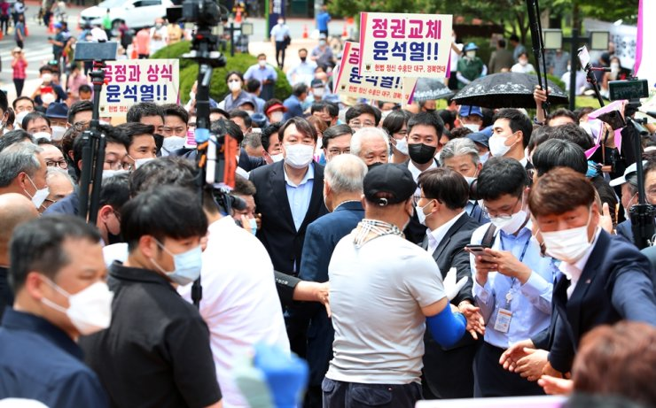 Supporters of independent candidate Yoon Seok-youl, center, hold signs during his visit to a democracy monument in Daegu, Tuesday. Yonhap