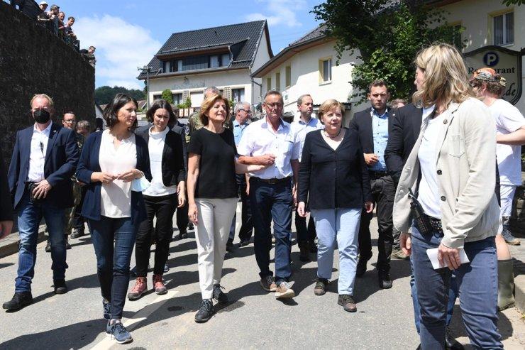 German Chancellor Angela Merkel, center right, and Rhineland-Palatinate State Premier Malu Dreyer, center left, walk during their visit to the flood-ravaged areas near Bad Neuenahr-Ahrweiler, Rhineland-Palatinate state, western Germany, Sunday. AFP-Yonhap