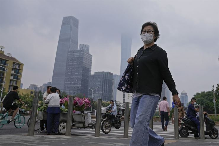A woman wearing a face mask to help curb the spread of the coronavirus walks by a vendor selling flowers outside a subway station in Beijing, Thursday. AP-Yonhap
