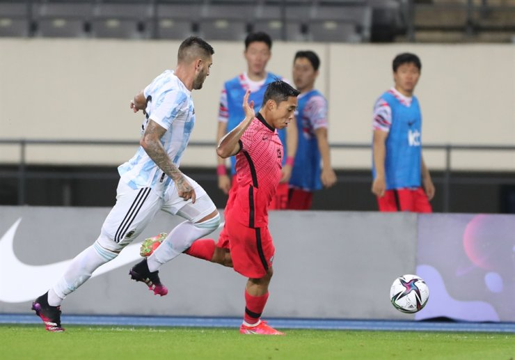 The South Korean Olympic football team's striker Lee Dong-jun, right, dribbles past an Argentinian defender during the two teams' exhibition match at Yongin Mireu Stadium in Gyeonggi Province, July 13. / Yonhap