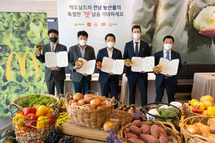 South Jeolla Governor Kim Yung-rok, center, and McDonald's Korea Managing Director Antoni Martinez, second from right, pose for a picture after signing an MOU to expand the use of domestic agricultural products at McDonald's restaurants in Mokpo, South Jeolla Province, Tuesday. Courtesy of McDonald's Korea