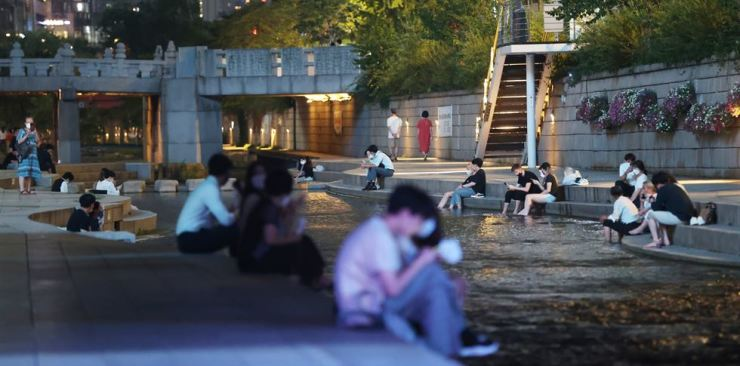 Seoul residents relax by Cheonggye Stream in central Seoul, July 22, when the city had a tropical night. Yonhap